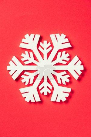 Foto de Vista superior del copo de nieve de papel sobre fondo rojo - Imagen libre de derechos