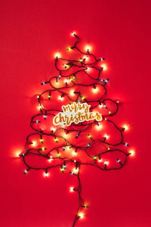 Colourful garlands in the form of christmas tree with Merry Christmas sign on red background