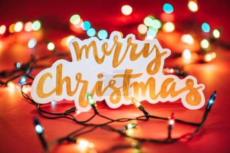 Photo for Merry Christmas sign on the background of shining garlands - Royalty Free Image