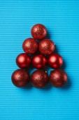 Flat lay of red shiny decorative christmas balls on the blue background
