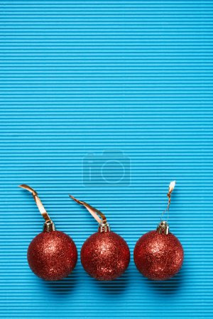 top view of red shiny decorative christmas balls on the blue background