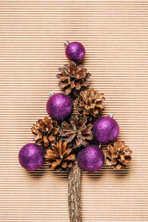 Photo for Flat lay of purple christmas balls and pine cones in the form of Christmas tree on the textured background - Royalty Free Image