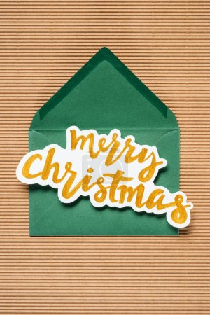 Flat lay of green envelope with yellow Merry Christmas sign