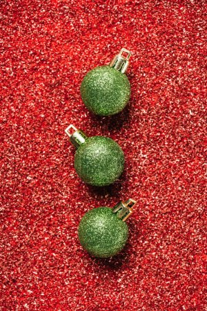 top view of green shiny decorative christmas balls on red sequin background