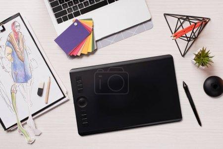 bureau avec ordinateur portable, des croquis, tablette graphique et stylet, plat poser