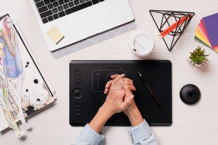 vue recadrée de concepteur holding mains au-dessus de bureau avec ordinateur portable, tablette graphique et stylet