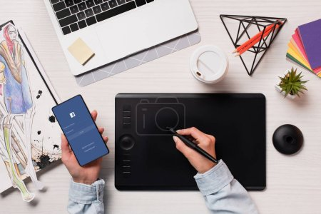 Photo for Cropped view of designer using graphics tablet, pen and smartphone with facebook on screen, flat lay - Royalty Free Image