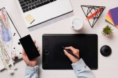 cropped view of designer using graphics tablet, pen and smartphone with blank screen, flat lay