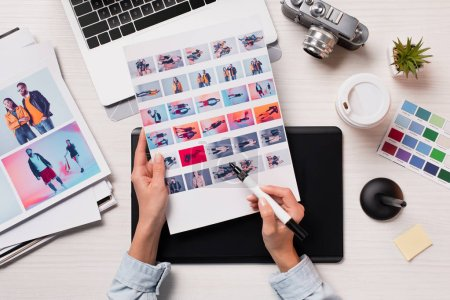 Photo for Office desk with cropped view of designer, artwork and laptop, flat lay - Royalty Free Image