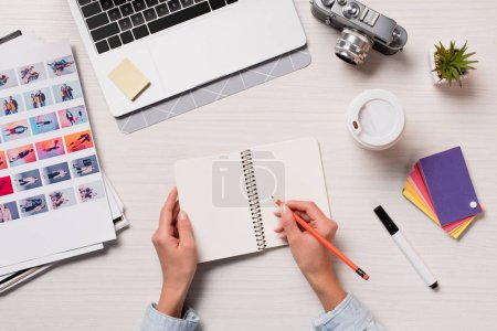 Photo for Cropped view of designer working at office desk and writing in notepad with laptop and designer supplies - Royalty Free Image