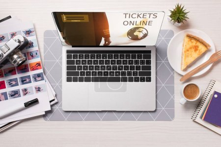 office desk with laptop with tickets online website on screen, flat lay