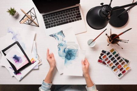 office desk with laptop, art supplies and cropped view of designer holding drawings, flat lay