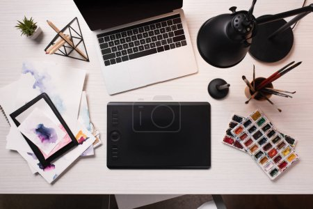 office desk with laptop, graphics tablet, pen and art supplies, flat lay