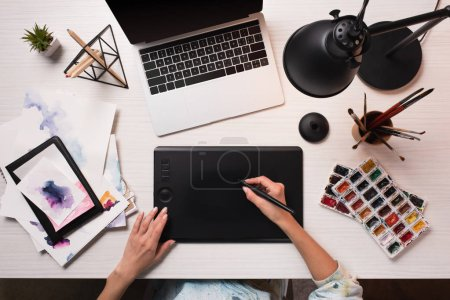 office desk with laptop, art supplies and cropped view of designer using graphics tablet and pen, flat lay