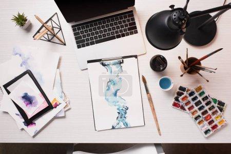 Foto de Escritorio de oficina con ordenador portátil, bocetos y arte suministros, planos pone - Imagen libre de derechos