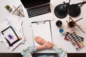 cropped view of designer at office desk with laptop, art supplies, flat lay