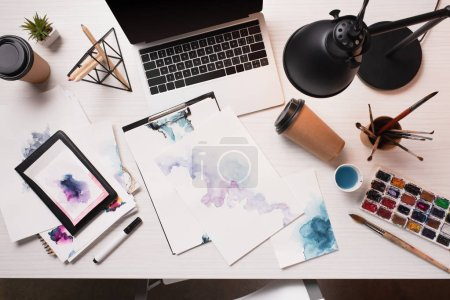 Photo for Flat lay of messy office desk with laptop, sketches and art supplies - Royalty Free Image