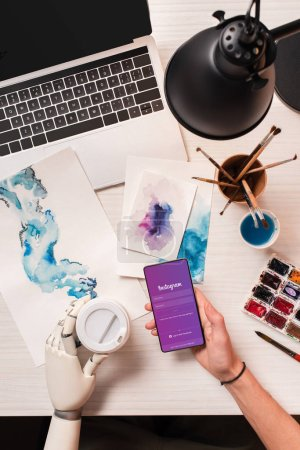 Photo for Top view of cropped female hand at designer office desk with robot hand holding smartphone with instagram app on screen - Royalty Free Image