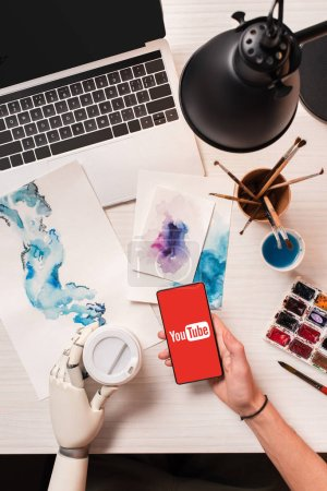 Photo for Cropped view of designer at office desk with robot hand holding smartphone with youtube app on screen - Royalty Free Image