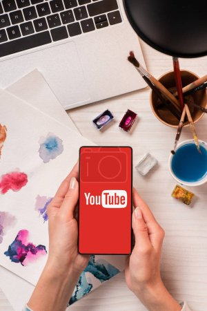 cropped view of designer at office desk holding smartphone with youtube app on screen, flat lay