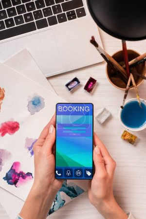 cropped view of designer at office desk holding smartphone with booking app on screen, flat lay