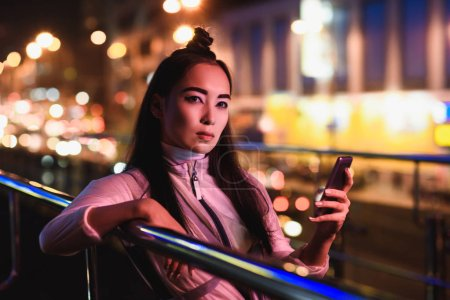 attractive asian girl holding smartphone on street with neon light and looking at camera, city of future concept