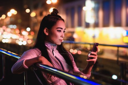 attractive asian girl using smartphone on street with neon light in evening, city of future concept