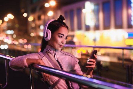 attractive asian girl listening music with smartphone on street with neon light in evening, city of future concept