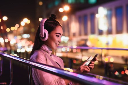 side view of smiling asian girl listening music with smartphone on street with neon light in evening, city of future concept