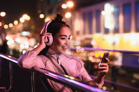 happy attractive asian girl listening music with smartphone on street with neon light in evening, city of future concept
