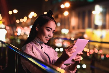attractive asian girl using tablet on street with neon light in evening, city of future concept