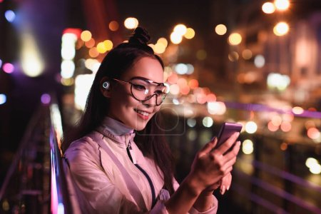 attractive asian girl with wireless earphone and glasses using smartphone on street with neon light, city of future concept