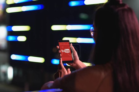back view of girl holding smartphone with loaded youtube page on street with neon light in evening, city of future concept