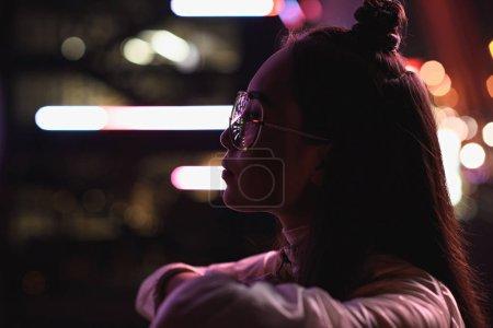 Foto de Vista lateral del estilo asiatico en gafas mirando lejos en la calle con luz de neón en la noche, la ciudad del futuro concepto - Imagen libre de derechos