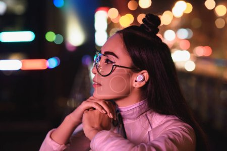 side view of stylish asian girl in glasses and wireless earphone looking away on street with neon light in evening, city of future concept