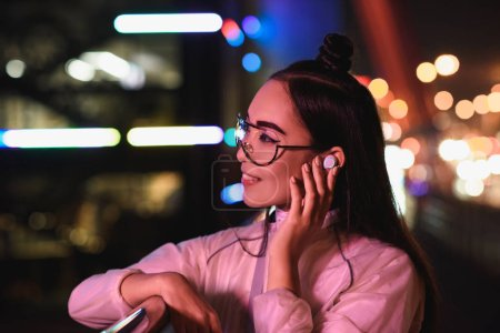 stylish asian girl in glasses touching wireless earphone on street with neon light in evening, city of future concept