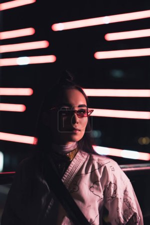 Photo for Attractive asian girl in white kimono and sunglasses standing on street with neon light in evening, city of future concept - Royalty Free Image