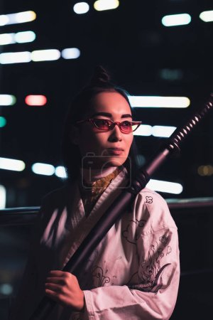 attractive asian girl in white kimono holding sword on street with neon light in evening, city of future concept