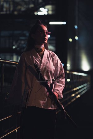 attractive asian girl in white kimono holding katana on street with neon light in evening, city of future concept
