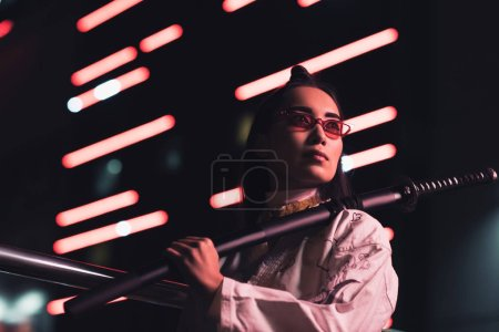 low angle view of attractive asian girl in white kimono holding japanese sword on street with neon light in evening, city of future concept