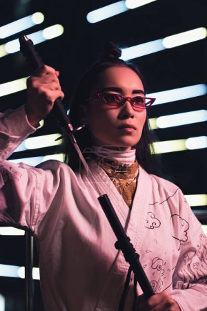 attractive asian girl in white kimono taking katana on street with neon light in evening, city of future concept