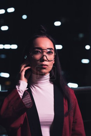 attractive asian girl in burgundy kimono and wireless earphone standing on street with neon light in evening, city of future concept