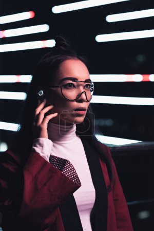 Photo for Attractive asian girl in burgundy kimono and wireless earphone looking away on street with neon light in evening, city of future concept - Royalty Free Image