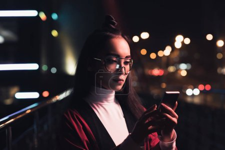 attractive asian girl in burgundy kimono and glasses using smartphone on street with neon light in evening, city of future concept