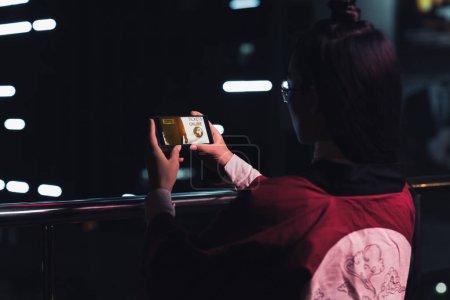Photo pour Vue arrière du jeune fille tenant smartphone avec appareil en ligne de billets sur rue avec néon en soirée, la ville du futur concept - image libre de droit