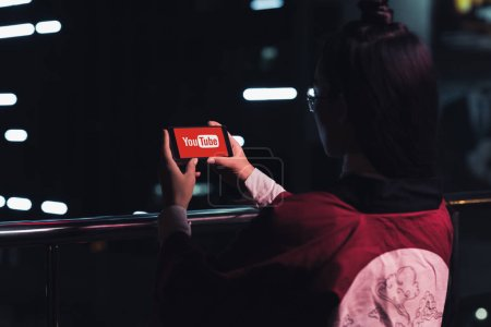back view of girl holding smartphone with youtube website on street with neon light in evening, city of future concept