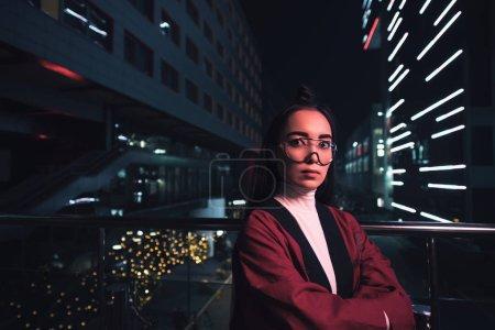 Foto de Hermosa chica en kimono Borgoña y gafas mirando a cámara en la calle en la noche, la ciudad del futuro concepto - Imagen libre de derechos