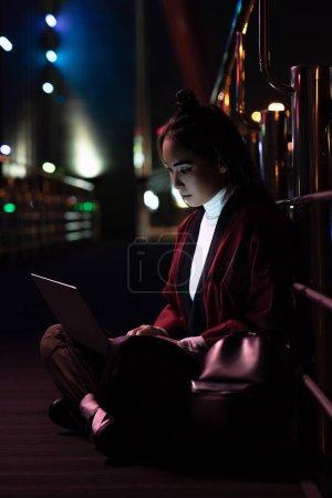 Photo pour Attrayant asiatique fille dans kimono assis et en utilisant ordinateur portable sur la rue avec néon lumière, ville de concept futur - image libre de droit