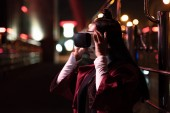 attractive asian girl using virtual reality headset on street in evening, city of future concept
