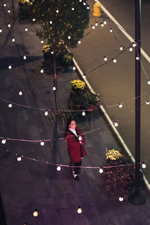 Foto de Vista de ángulo alto de atractiva chica en kimono Borgoña caminando en la calle en la noche, la ciudad del futuro concepto - Imagen libre de derechos